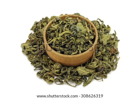green tea leaves in a wooden bowl on a white background - stock photo