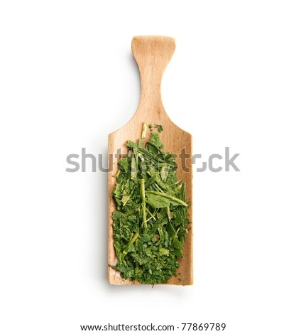 Green tea leaves on a wooden tea spoon - stock photo