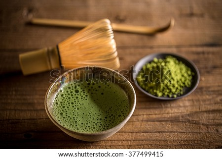 Green tea matcha in a bowl with whisk and spoon - stock photo