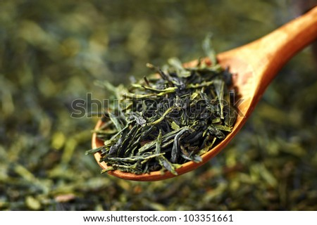 Green tea on wooden spoon - stock photo