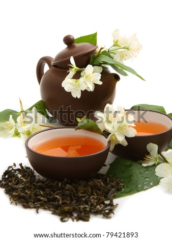 Green tea with fresh jasmine leaves and flowers on white background