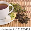green tea with herbs and lemon on bamboo mat background - stock photo