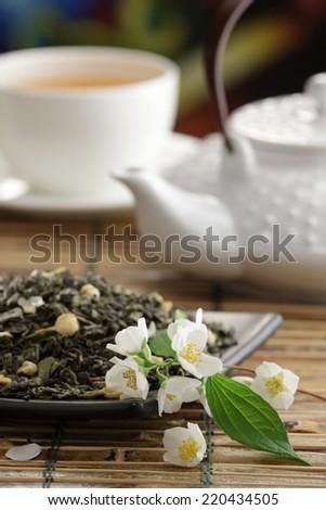 Green tea with jasmine flowers, green tea leaves, tea  cup and tea pot on bamboo table - stock photo