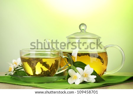 green tea with jasmine in cup and teapot on wooden table on green background - stock photo