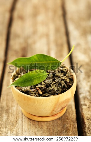 Green tea with leaf in bowl on old wooden table - stock photo