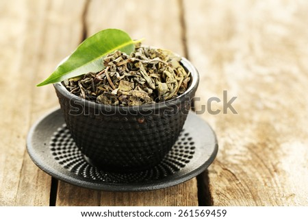 Green tea with leaf in cup on old wooden table - stock photo