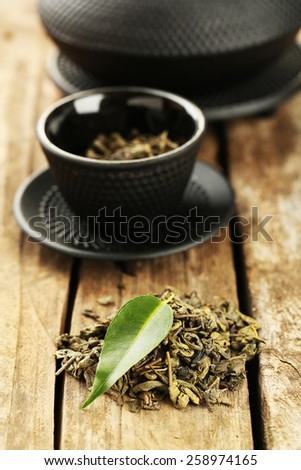 Green tea with leaf on old wooden table - stock photo