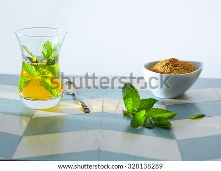 green tea with mint Moroccan style on wood blue white table - stock photo