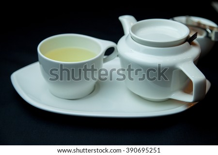 green tea with sugar in cup and teapot