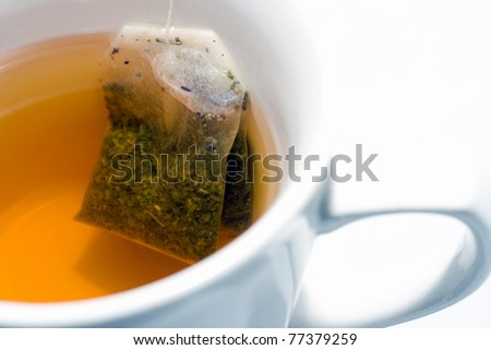 Green teabag in white cup taken close up from above - stock photo