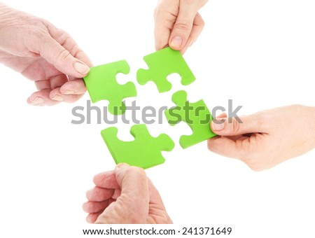Green Teamwork - group of people holding green jigsaw puzzle pieces