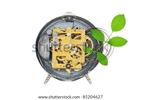Green technology - antique vintage alarm clock mechanism and plant - stock photo