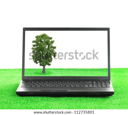 Green technology. Laptop on the grass with a tree on the screen - stock photo