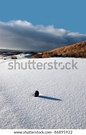 green tee on a snow covered links golf course in ireland in winter - stock photo