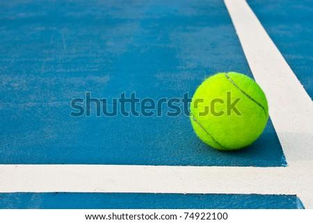 Green tennis ball on blue court - stock photo