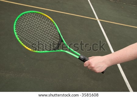 green tennis racket in a woman's hand in front of a tennis court - stock photo