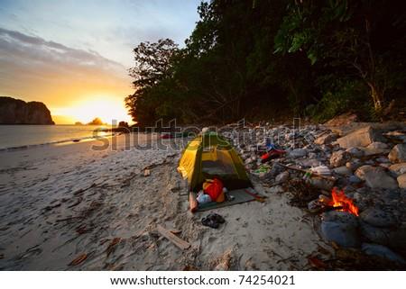 Green tent on sandy wild beach at sunset light - stock photo