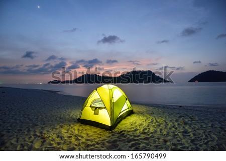 Green tent on sandy wild beach at twilight - stock photo