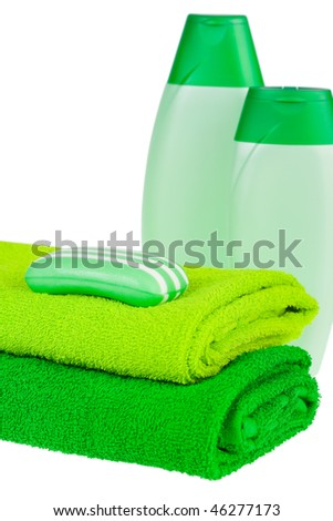 Green terry towels, soap and shampoo on white background. Isolated