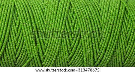 green  thread, textured background - stock photo