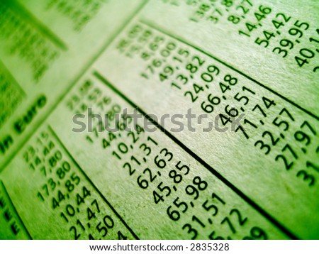 green tinted close up of financial part of newspaper showing stock numbers.