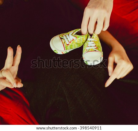 Green tiny shoes on the belly of pregnant - stock photo