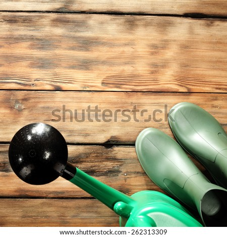 green tools shoes and brown old worn floor of spring time  - stock photo