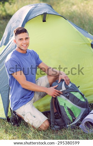 Green tourism.  Portrait of a young handsome tourist wearing blue t-short and beige shorts, sitting in the field fastening his bag smiling, green tent near - stock photo