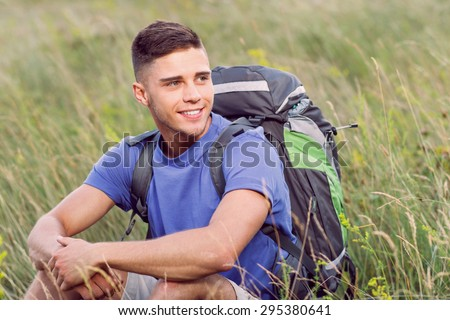 Green tourism.  Portrait of a young handsome tourist wearing blue t-short and beige shorts, sitting on the plaid wearing backpack looking aside smiling - stock photo