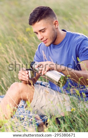 Green tourism.  Portrait of a young handsome tourist wearing blue t-short and beige shorts, sitting on the plaid drinking tea from thermos  - stock photo