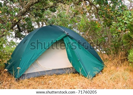 green touristic  tent in a morning forest - stock photo
