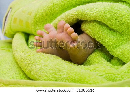 Green towel around cute newborn feet - stock photo