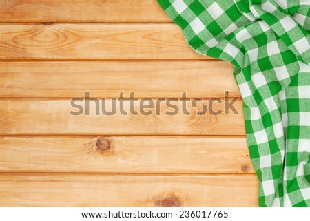 Green towel over wooden kitchen table. View from above with copy space - stock photo