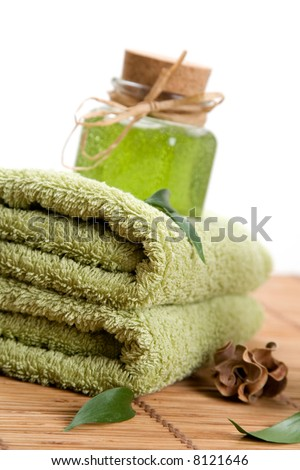 Green towels and liquid soap in glass jar