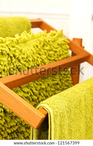 Green towels hanging on a wooden towel rail - stock photo