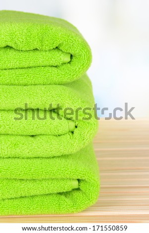 Green towels on table on light background