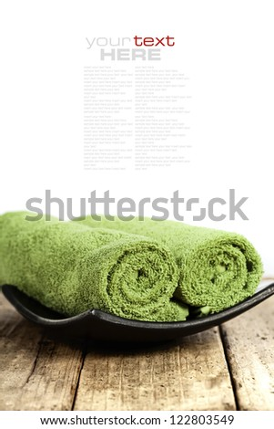 Green towels on the wooden board (with easy removable sample text) - stock photo