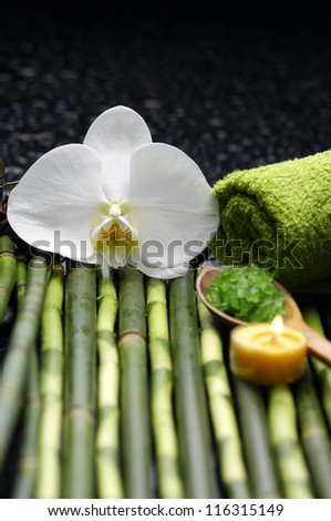 green towels, salt in spoon and white orchid on bamboo grove - stock photo