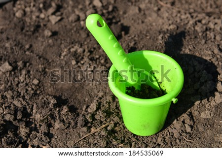 green toy bucket and spade in the mud - stock photo