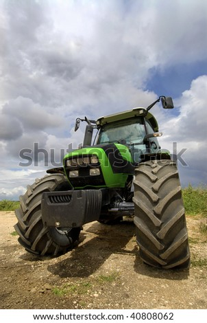 Green tractor in the field with a cloudy sky - stock photo