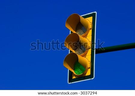 Green traffic light on blue sky - stock photo
