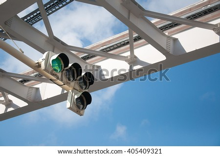 Green traffic light on the blue clear sky background - stock photo