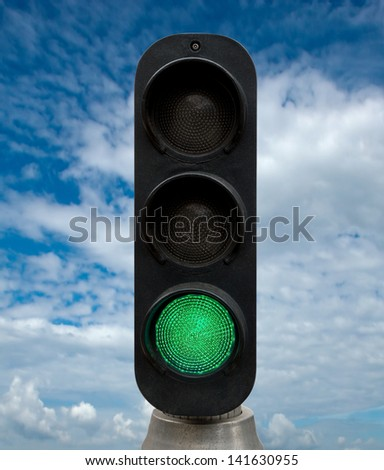 Green traffic lights against blue sky backgrounds. Clipping Path included. - stock photo