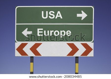 green traffic sign in front of a blue sky, horizontal arrows showing two directions and a red white road warning post. Business concept for the relations or conflicts between two Nations: USA, Europe - stock photo
