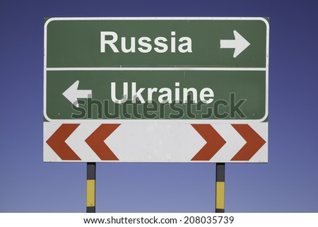 green traffic sign in front of a blue sky, horizontal arrows showing two directions and a red white road warning post. Business concept for the relations or conflicts between  Russia, Ukraine - stock photo