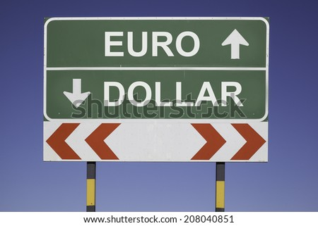 green traffic sign in front of a blue sky, horizontal arrows showing two directions and a red white road warning post. Business fiscal concept for currency exchange rate, Euro  up and Dollar down - stock photo