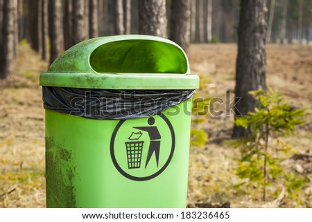 Green trash basket with sign pictogram in forest, plastic bag inside visible. - stock photo