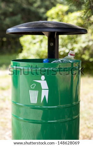 Green trash basket with sign pictogram, plastic bottles visible. - stock photo