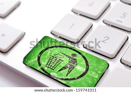 Green trash button on white keyboard - stock photo