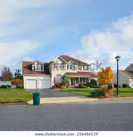 Green trash container at driveway edge on street suburban home autumn day residential neighborhood USA blue sky clouds